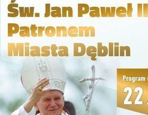 """Fragment plakatu promującego wydarzenie, napis: """"Św, Jan Paweł II Patronem Miasta Dęblin"""", pod napisem zdjęcie Papieża Jana Pawła II"""