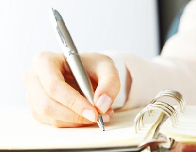 Ręka trzymająca długopis i pisząca po kartce