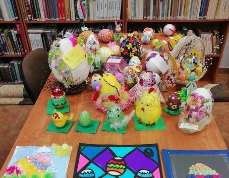 Zdjęcie przedstawia jajka wielkanocne wykonane różnymi technikami, które są ustawione na biurku. Mają one kształty kurczaczków, zajączków, pisanek, koszyczków wielkanocnych.