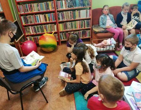 Zdjęcie przedstawia dzieci skupione na kanapie i dywanie. Na pierwszym planie jest chłopiec siedzący na krześle i czytający książkę. W tle stoją regały z książkami.