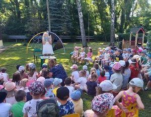 Na zielonej trawie na żółtych krzesełkach siedzą przedszkolaki, dalej stoi bibliotekarz z mikrofonem i z książką w ręku, w tle znajdują się drzewa i plac zabaw