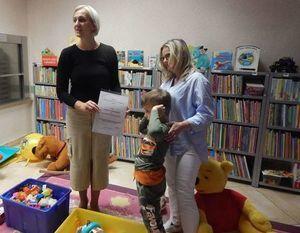 Na zdjęciu Pani Dyrektor MBP otrzymuje od chłopca podziękowanie, obok stoi Pani z przedszkola.