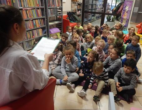 Na zdjęciu bibliotekarka z przedszkolakami