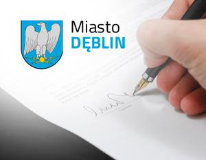 Grafika ogólna- napis miasto Dęblin, herb, dłoń z długopisem pisząca po dokumencie