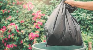Czarny worek wrzucany do śmieci