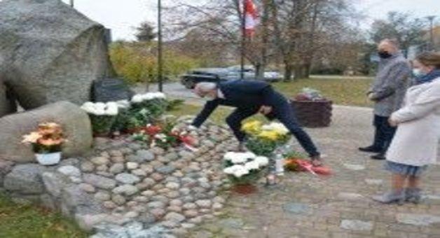 Ludzie w maseczkach składający kwiaty przy pomniku