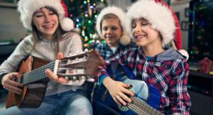 Troje dzieci śpiewa kolędy, dwoje gra na gitarach