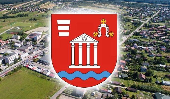 Zdjęcie przedstawia herb gminy na tle zdjęcia lotniczego