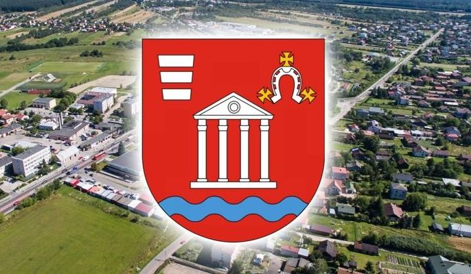 Herb gminy na tle budynków