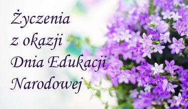 Na zdjęciu napis Życzenia z okazji Dnia Edukacji Narodowej na tle kwiatów