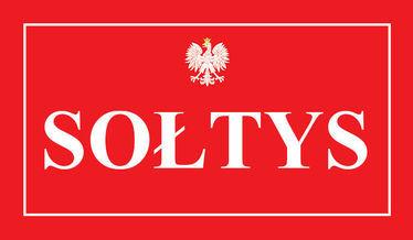 Na zdjęciu godło państwowe z napisem Sołtys na czerwonym tle