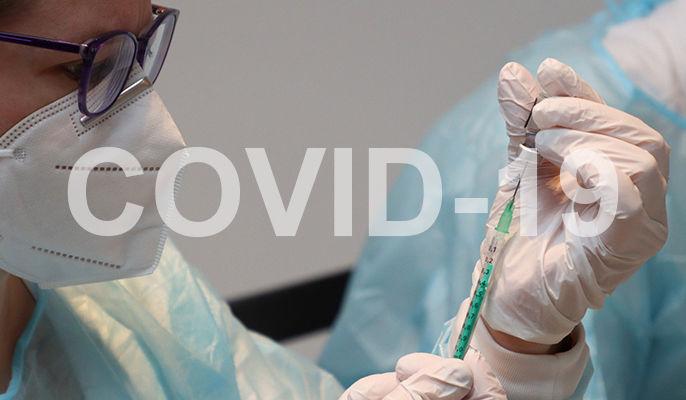 Na zdjęciu medyk ze szczepionką i napis covid-19