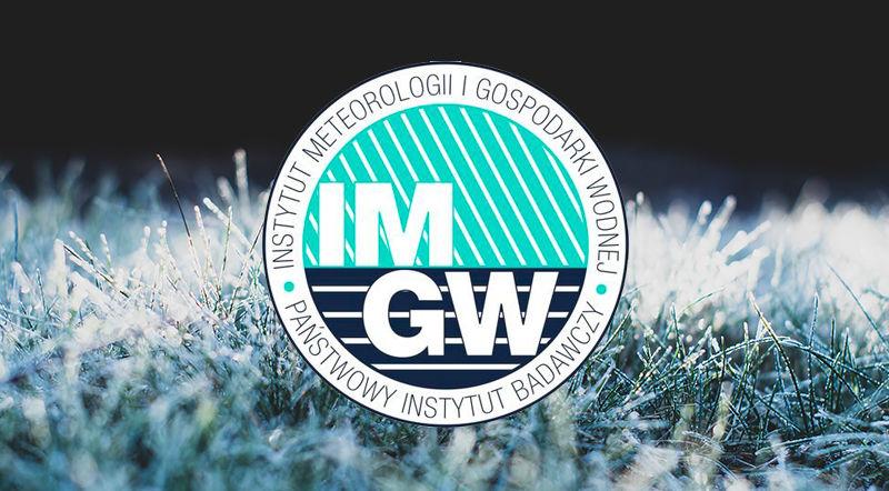 Logo IMGW na tle zmarzniętej trawy