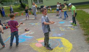Zdjęcie przedstawia rysujące kredą dzieci