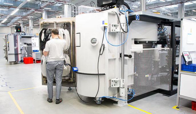 Zdjęcie przedstawia pracownika podczas obsługi maszyny