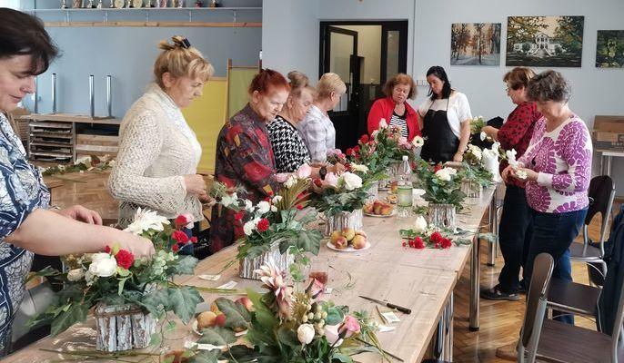 Na zdjęciu kobiety układające kwiaty.