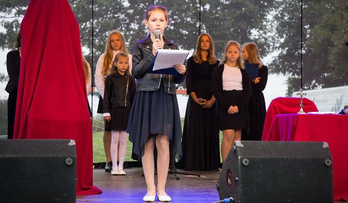 Na zdjęciu uczennica przemawiająca na scenie