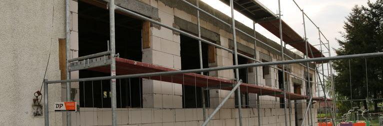 Zdjęcie przedstawia budynek i ustawione obok niego rusztowania