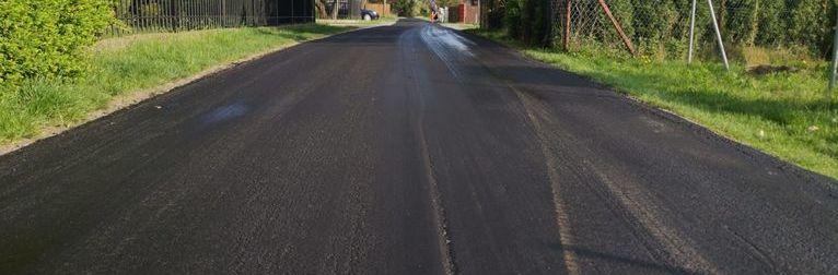 Zdjęcie przedstawia nowowylany asfalt na drodze