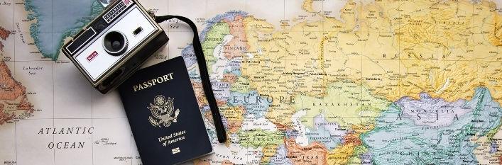 Mapa świata a na niej leży paszport i aparat
