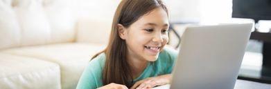 Uśmiechnięta dziewczynka przy laptopie