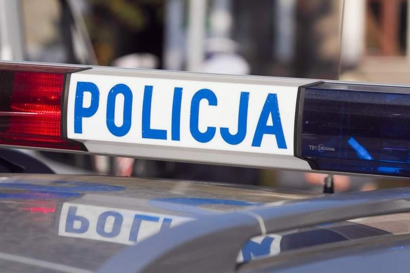 Fragment radiowozu z napisem POLICJA