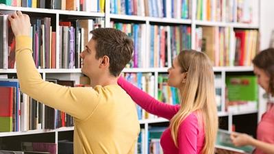 kobieta i mężczyzna sięgający po książki z półki