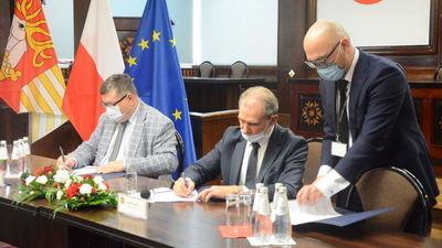 trzech mężczyzn przy stole podpisujący dokumenty