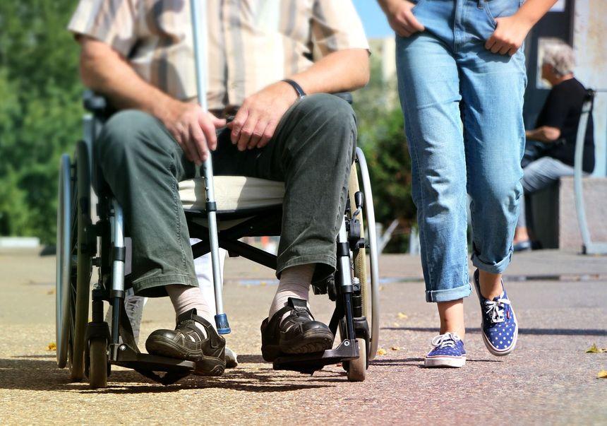 mężczyzna na wózku inwalidzkim w towarzystwie opiekuna