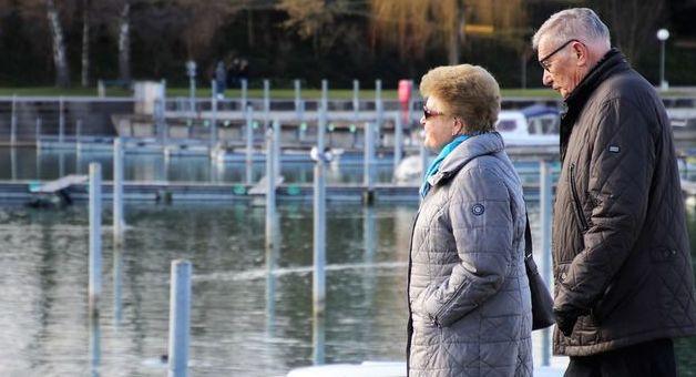 Grafika przedstawia dwójkę starszych spacerujących osób nad zbiornikiem wodnym