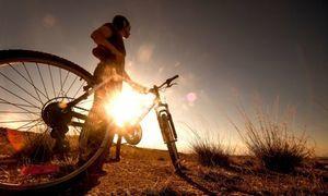 Rowerzysta z rowerem przy zachodzie słońca