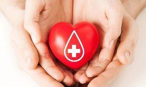Czerwone serce ze znakiem kropli i krzyżyka w dłoniach dwóch osób