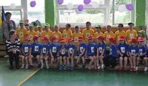 Dzieci w żółtoniebieskich strojach siedzące na sali gimnastycznej z nauczycielami