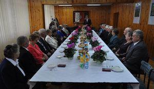 Na zdjęciu uczestnicy spotkania siedzą za długim stołem