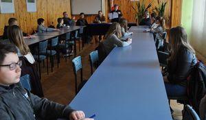 Uczestnicy turnieju siedzący przy stołach przed komisją