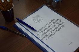 Zdjęcie przedstawia dokument leżący na biurku oraz długopisy