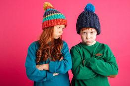 Zdjęcie przedstawia rudowłosą dziewczynkę oraz chłopca w czapkach na różowym tle