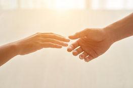 Zdjęcie przedstawia dwie dłonie na jasnym tle