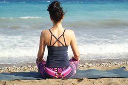 Grafika przedstawia medytującą kobietę na tle morza