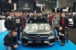 Zdjęcie przedstawia uczniów pozujących przy aucie marki Mercedes