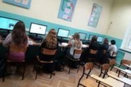 Zdjęcie przedstawia uczniów siedzących w klasie przy komputerach