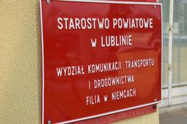 Tabliczka czerwona z napisami Starostwo Powiatowe w Lublinie Wydział Komunikacji, Transportu i Drogownictw