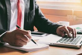 na zdjęciu znajduje się mężczyzna z siedzący przy biurku z długopisem w ręku