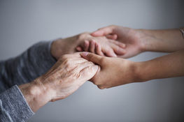 zbliżenie dwóch osób trzymających się za ręce w geście wsparcia i pomocy