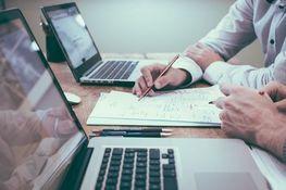 na zdjęciu znajdują się dwie osoby siedzące przed laptopami, oglądające dokumenty leżące na biurku