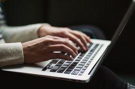 na zdjęciu znajduje się zbliżenie rąk ułożonych na klawiaturze laptopa