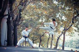 dwie osoby walczące taekwondo na ulicy