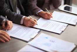na zdjęciu znajduje się zbliżenie na trzy męskie dłonie podpisujące dokumenty