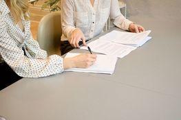 na zdjęciu znajdują się dwie kobiety dyskutujące nad leżącymi na stole teczkami z dokumentami
