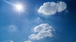 słońce na błękitnym niebie, dwie chmurki obok